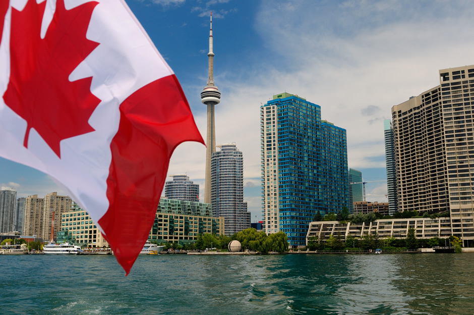 Toronto's lakeshore as observed on a boat. The Canadian Flag is flying.