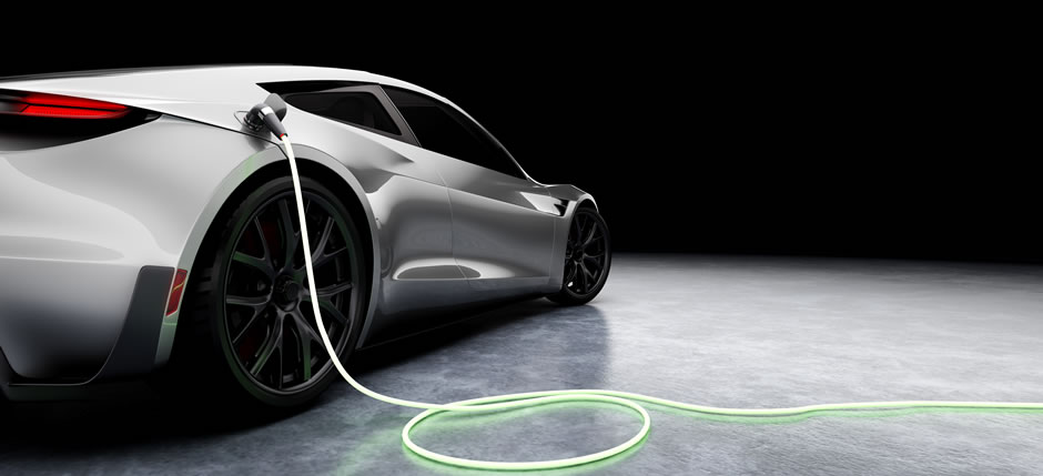 A silver electric sports car charging against a black background