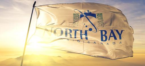 Flag of North Bay, Ontario waving on top of a sunrise