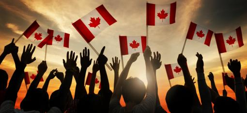 Canadians celebrating and raising the Maple Leaf flag
